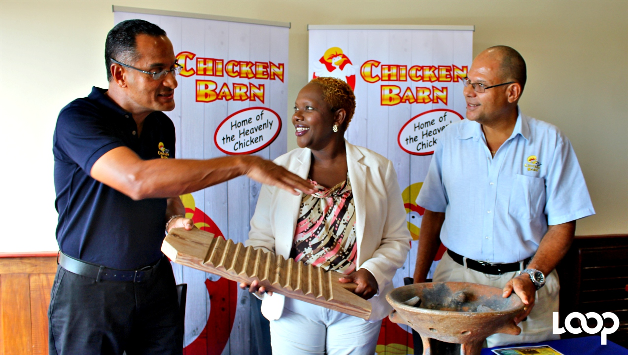 Paul Hynam (left) and Peter Hynam (right), Directors of Chicken Barn Ltd., and Courts e-Commerce Supervisor, Tisha Dhayle, with a jucking board and coal pot as they discuss all things Bajan at the launch of the Chicken Barn Independence Treasure Hunt.