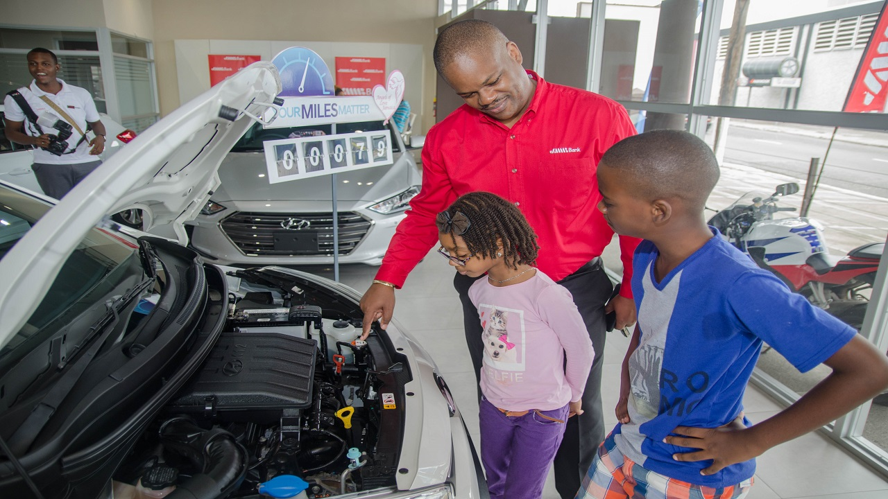 Owen Ferguson, Branch Manager, JMMB Bank examines the engine of the new Hyundai Grand i10 with his son Jaiden, and Madison.