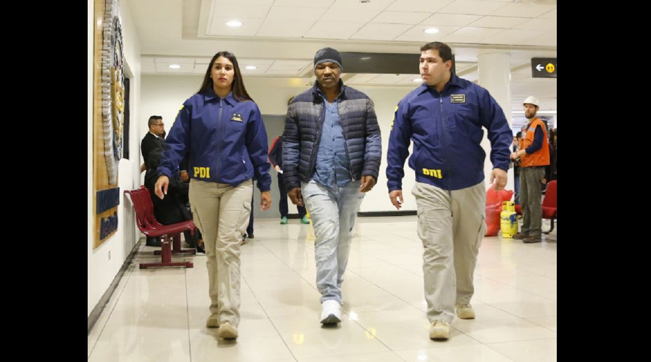 In this photo provided by the Policia de Investigacion de Chile, PDI, officers escort former heavyweight boxing champion Mike Tyson after being denied entry to the country, at the international airport in Santiago, Chile, Thursday. (PHOTO: AP)