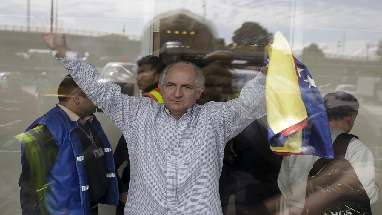 Holding a national Venezuelan flag, ousted Caracas Mayor Antonio Ledezma waves from inside El Dorado international airport, as he prepares for departure, in Bogota, Colombia, Friday, Nov. 17, 2017.