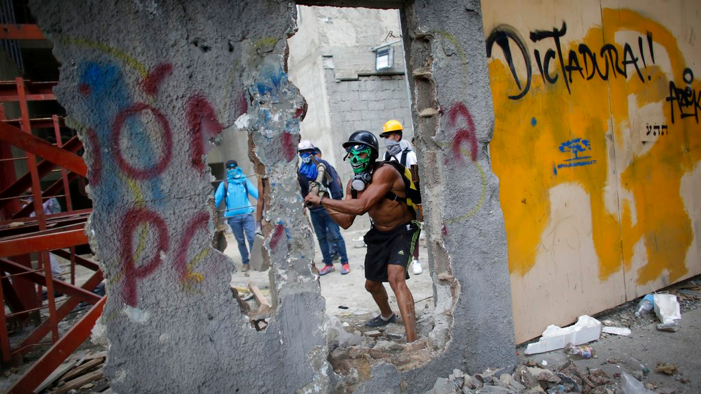 An anti-government demonstrator whacks a a wall to release pieces of concrete to throw at Venezuelan Bolivarian National Police, during a protest against the installation of a constitutional assembly in Caracas, Venezuela, Friday, Aug. 4, 2017. (AP Photo/Ariana Cubillos)