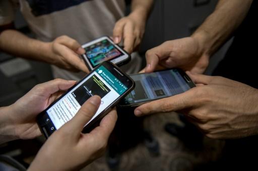 AFP / Mauro PIMENTEL  Les patients d'un groupe de désintoxication numérique montrent leurs téléphones portables, à Rio, le 20 octobre 2017