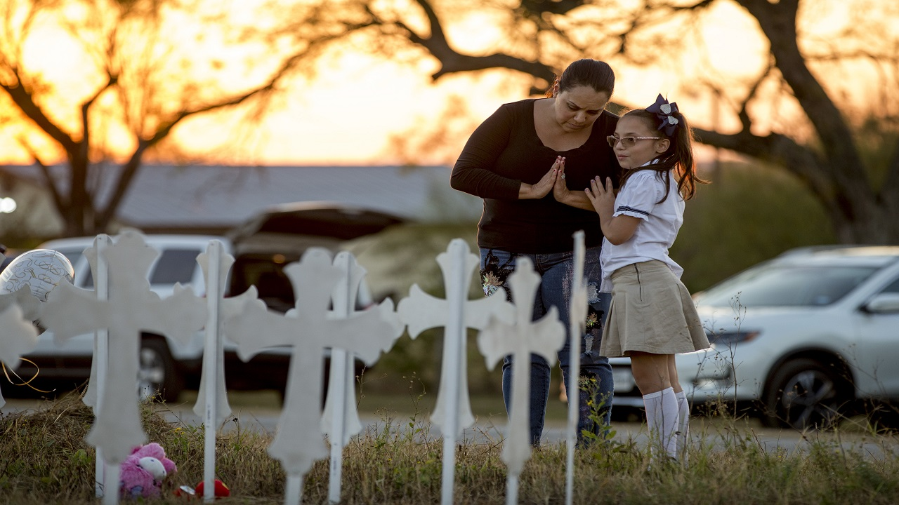 Meredith Cooper, of San Antonio, Texas, and her 8-year-old daughter, Heather, visit a memorial of 26 metal crosses near First Baptist Church in Sutherland Springs, Texas, Monday Nov. 6, 2017.