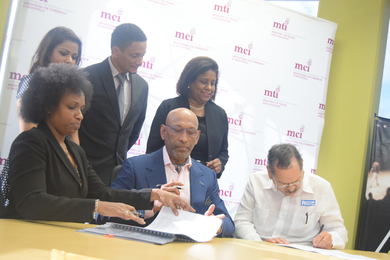 Trade & Industry Minister (back row) looks on as Professor Andrew Ramroop, Founder of the Savile Row Academy (centre), Professor Clement Imbert, Chairman MIC Institute of Technology (right) and Ms. Dionne Mc Nicol Stephenson, Director, CreativeTT (left) sign a collaborative agreement following the launch of the Ultra Bespoke Tailoring programme. Also looking on are Mr Jason Lindsay, Chairman FashionTT (centre) and Ms. Lisa-Marie Daniel, General Manager, FashionTT (back row, left)
