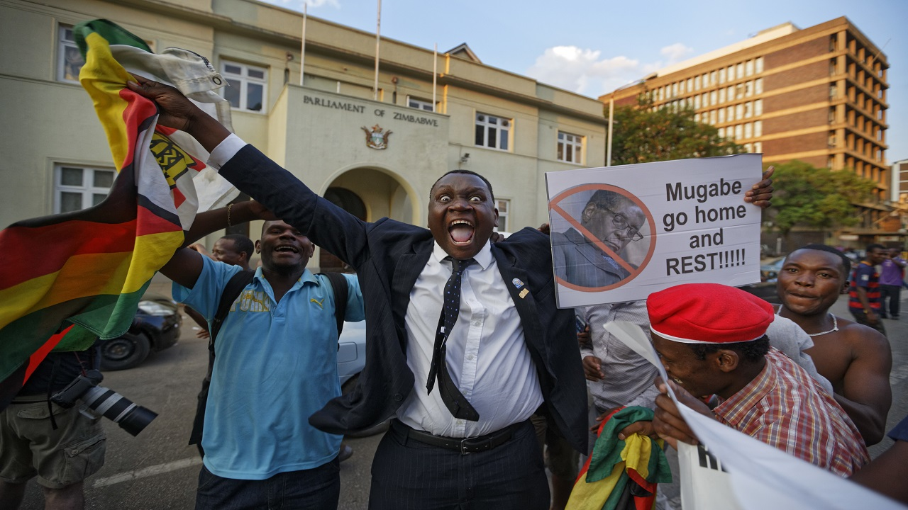 Zimbabweans celebrate outside the parliament building immediately after hearing the news that President Robert Mugabe had resigned, in downtown Harare, Zimbabwe Tuesday, Nov. 21, 2017.