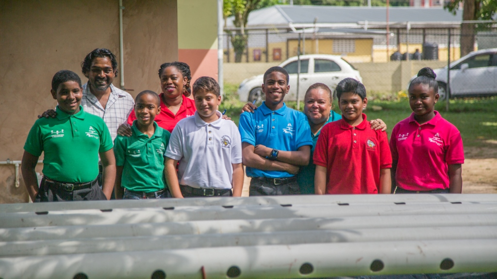 Students of the New Beginnings Special School proudly view the new Aquaponics Unit installed at the school.  With them are (Left Back) Eustace Phillip representative from the Ministry of Agriculture, Land and Fisheries and Cindyann Currency, Digicel Foundation Operations Manager