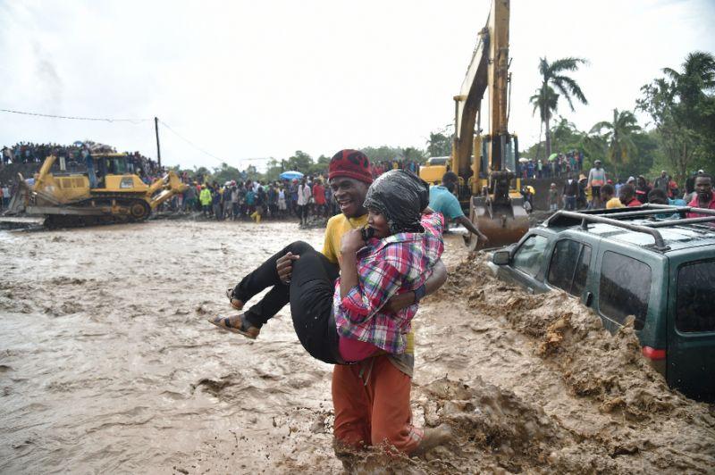Un homme aide une femme à traverser la rivière La Digue à Petit Goave où le pont s'est effondré lors du cyclone Matthew. Photo : AFP