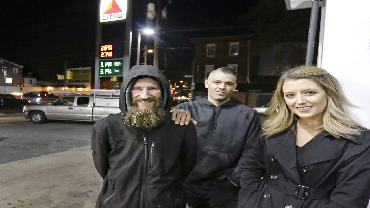 In this Nov. 17, 2017 photo, Johnny Bobbitt Jr., left, Kate McClure, right, and McClure's boyfriend Mark D'Amico pose at a CITGO station in Philadelphia.