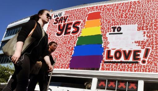 """AFP / William WEST  Des personnes passent devant un immense panneau d'affichage pour le """"oui"""" au mariage gay à Sydney le 14 bovembre 2017"""