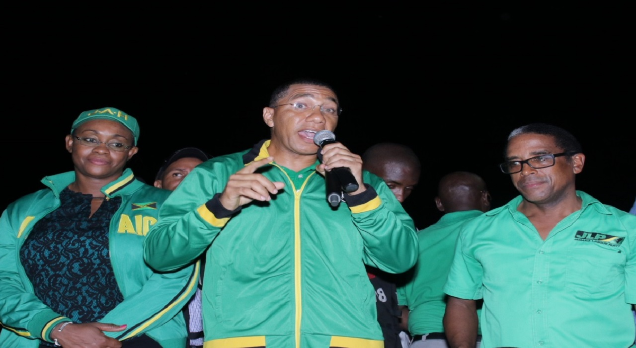 JLP leader Andrew Holness (centre) addresses labourites in South East St Mary after Monday's by-election. He's joined on stage by MP-elect Dr Norman Dunn and wife, MP Juliet Holness. (PHOTOS: Llewellyn Wynter)