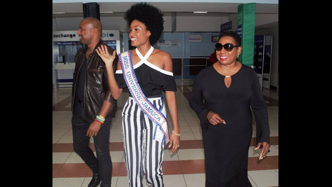 "Davina Bennett (centre) waves to supporters on her arrival at the Norman Manley International Airport in Kingston on Monday. She is accompanied by Minister of Culture, Gender, Entertainment and Sport, Olivia ""Babsy"" Grange."