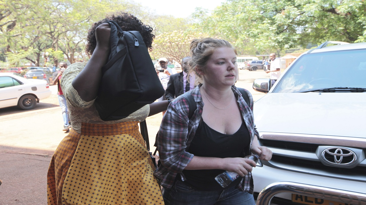 U.S. Citizen Martha O' Donovan, right, appears at the Harare Magistrates court escorted by a plain clothes police officer shielding her face in Harare, Saturday, November, 4, 2017. (PHOTO: AP)