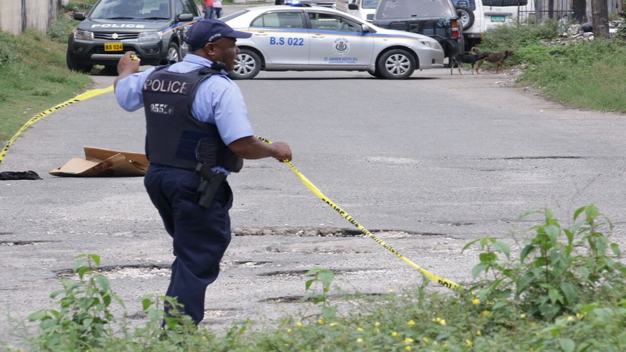 A police officer prepares to cordon a crime scene along Elma Crescent, off Washington Boulevard in St Andrew, with tape on Monday.