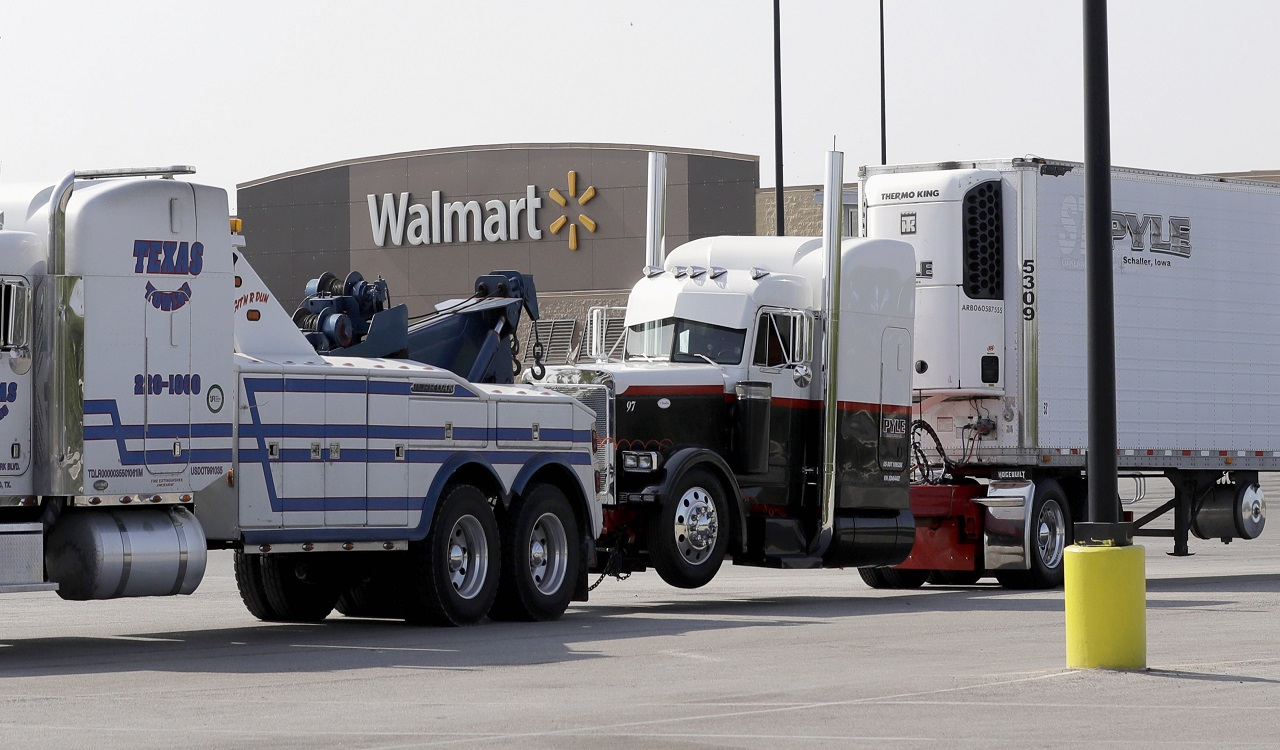 In this July 23, 2017, file photo, a Pyle Transportation-branded semitrailer, at right, is towed from the scene of a human trafficking case in which multiple immigrants died in San Antonio.