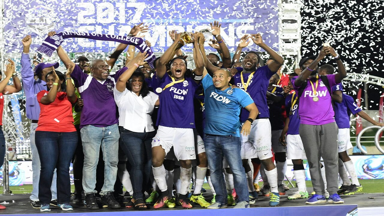Vice President of Marketing & TV FLOW Carlo Redwood (right) and Kingston College's captain Javain Brown (left) raise the Super Cup in celebration. Also sharing in the occasion are team members and officials. (PHOTO: MARLON REID)