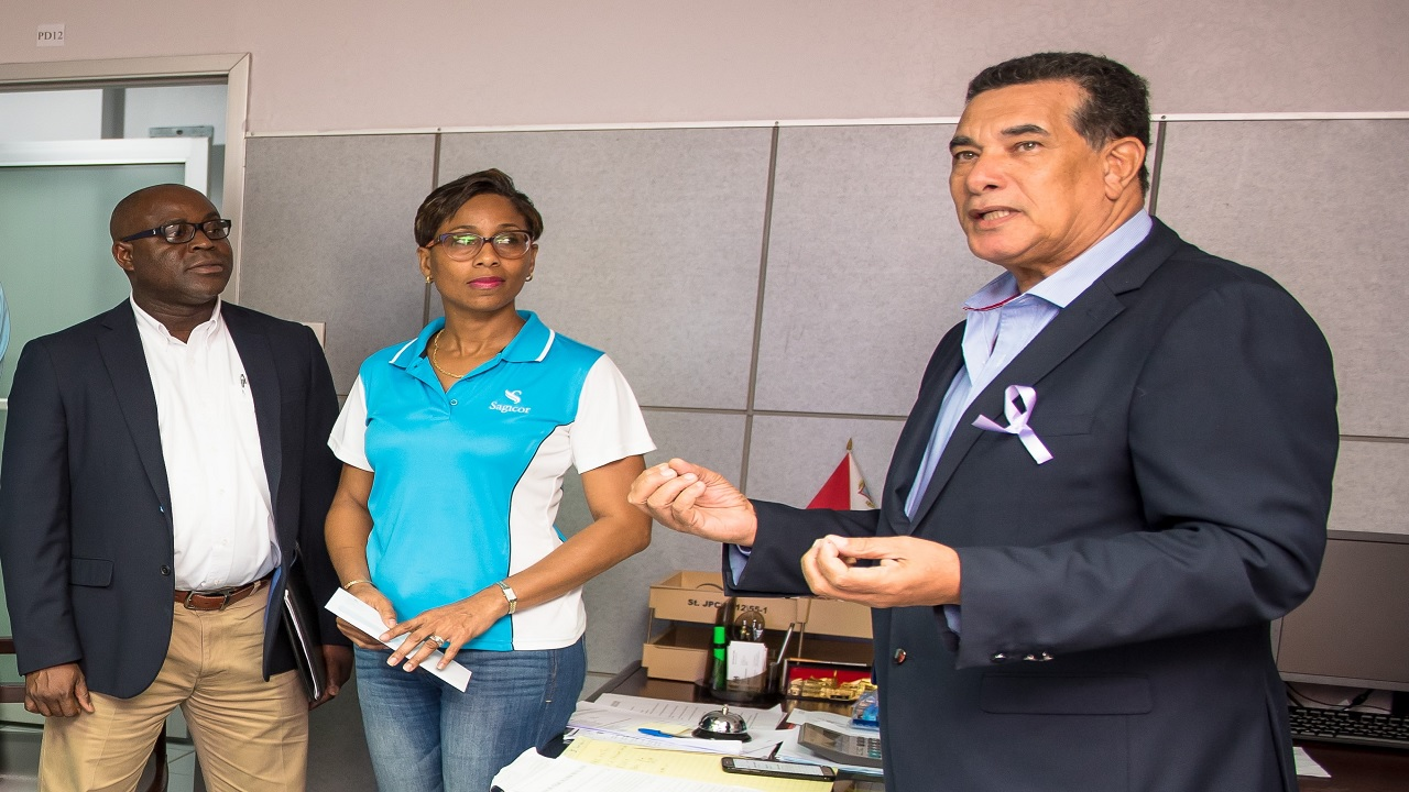 Errol Moss (left), Unit Manager - Sagicor Life, Montego Bay Branch and Wendy Bernard, Branch Manager, Sagicor Bank, Montego Bay with Mayor Homer Davis at the St. James Municipal Corporation, to make a symbolic presentation representing a five million donation from Sagicor to help the city of Montego Bay with recovery efforts following the recent floods that caused extensive damage.