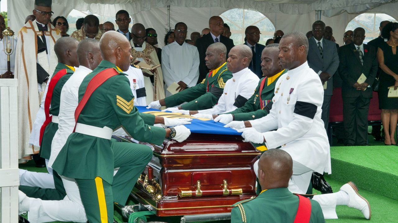Officers fold the Barbados flag over the casket of the late Sir Clifford Husbands. (PHOTO: BGIS)