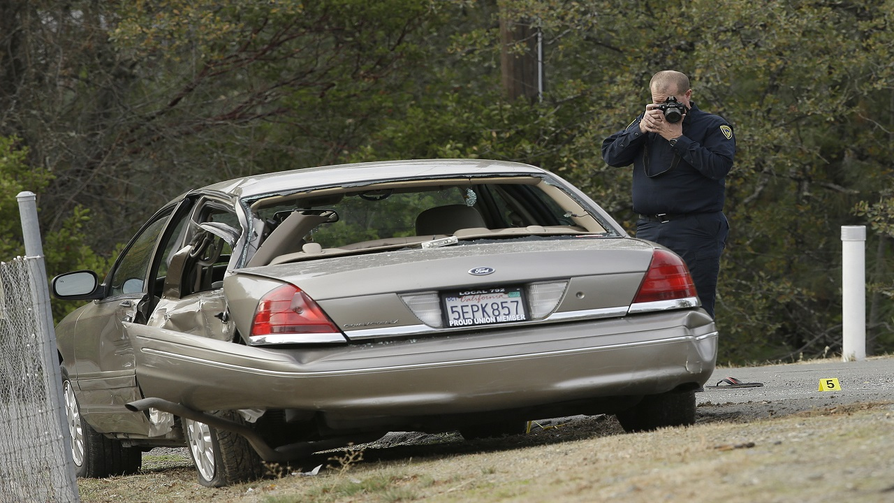 A California Highway patrol officer photographs a vehicle involved in a deadly shooting rampage at the Rancho Tehama Reserve, near Corning, Calif., Tuesday, Nov. 14, 2017.