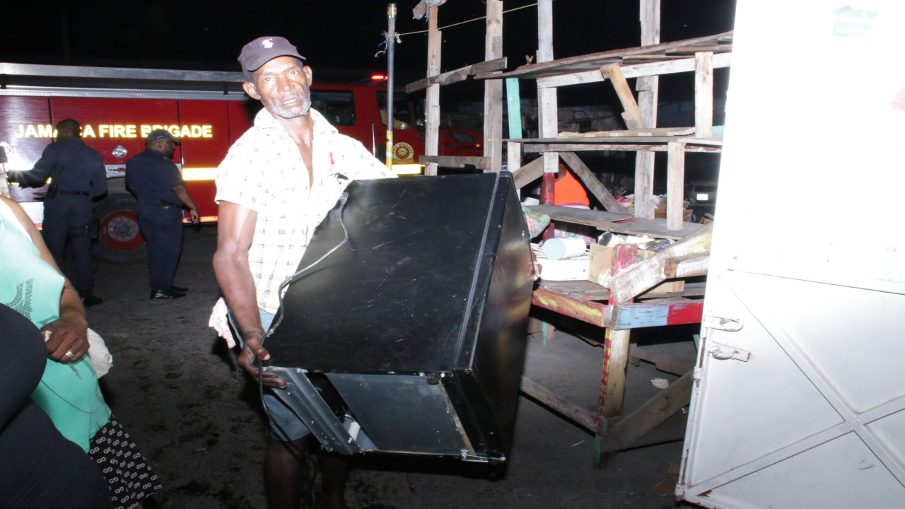 A man carries an item from the burning market on Tuesday morning. (PHOTOS: Llewellyn Wynter)