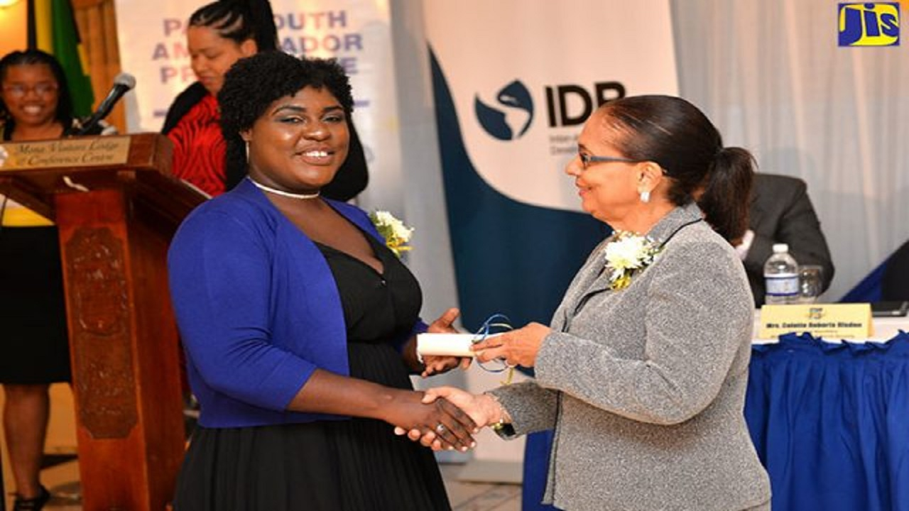 First-year medical student at the University of the West Indies, Mona, and one of the Ministry of Labour and Social Security's PATH 15th Anniversary Scholarship recipients, Jinelle Henry (left), collects her award from Labour Minister Shahine Robinson. (PHOTO: JIS)