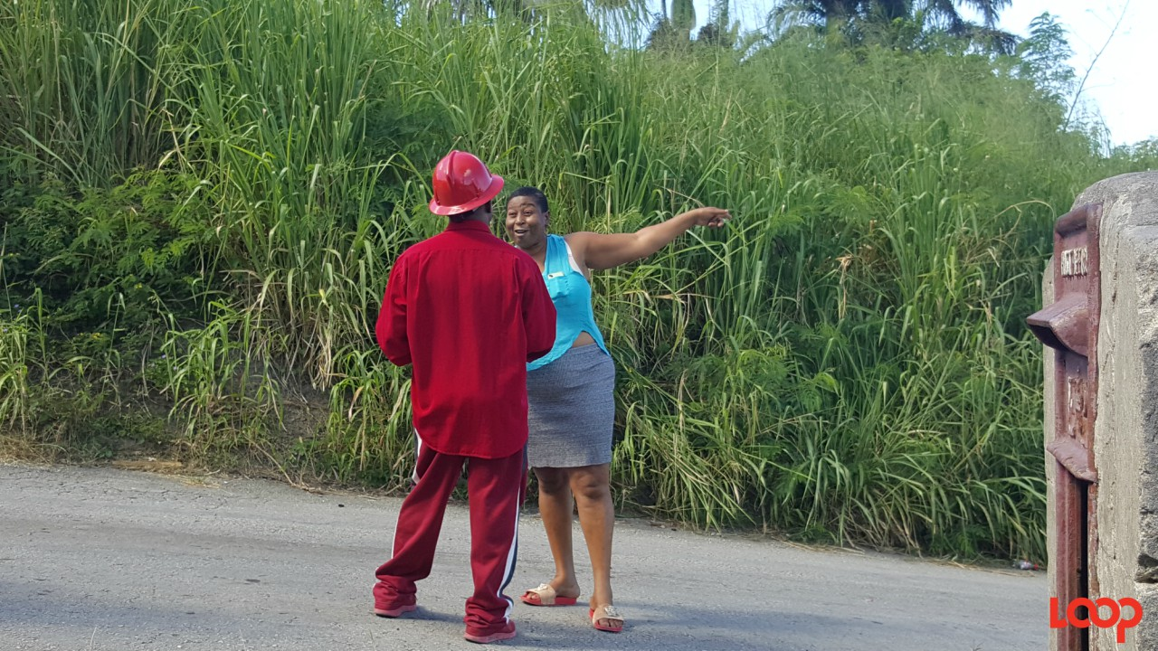 Resident point towards the direction of her home as she confronts the MP for St. Andrew, George Payne.