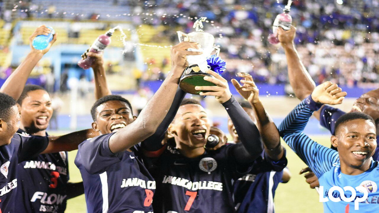 Jamaica College players hoist the ISSA/FLOW Walker Cup trophy after beating Kingston College in the finals at the National Stadium on Tuesday. (PHOTOS: Marlon Reid)