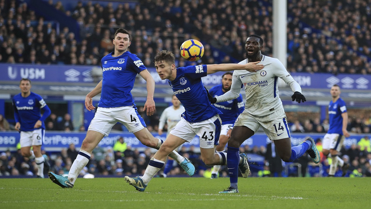 Everton's Jonjoe Kenny, centre and Chelsea's Tiemoue Bakayoko battle for the ball, during their English Premier League football match  at Goodison Park, in Liverpool, England, Saturday Dec. 23, 2017.