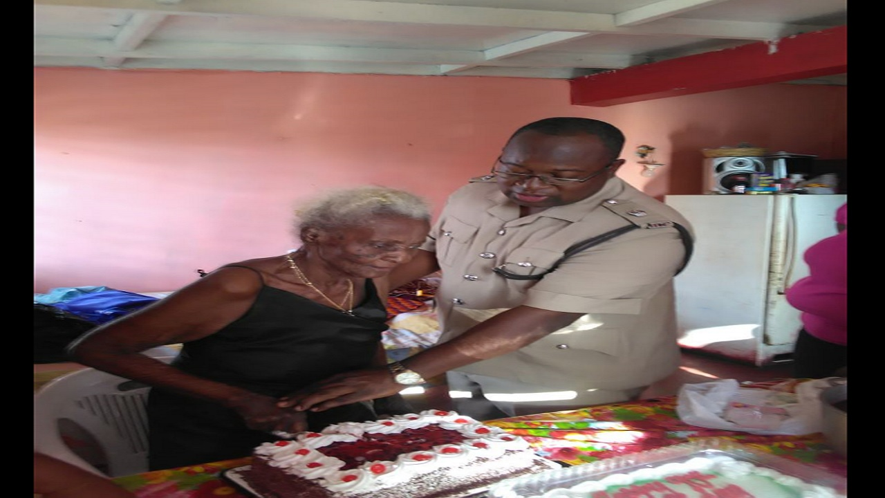 Superintendent of Kingston Western, Howard Chambers cuts the birthday cake with senior citizen, Juanita Rose.