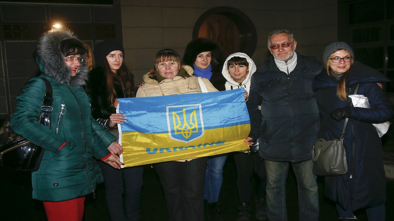 Relatives and friend of the Ukrainian prisoners held by the rebels hold a Ukrainian National flag as they wait them at the Kiev's airport in Kiev, Ukraine, Wednesday, Dec. 27. Ukrainian authorities and Russian-backed separatist rebels conducted a massive prisoner exchange on Wednesday.
