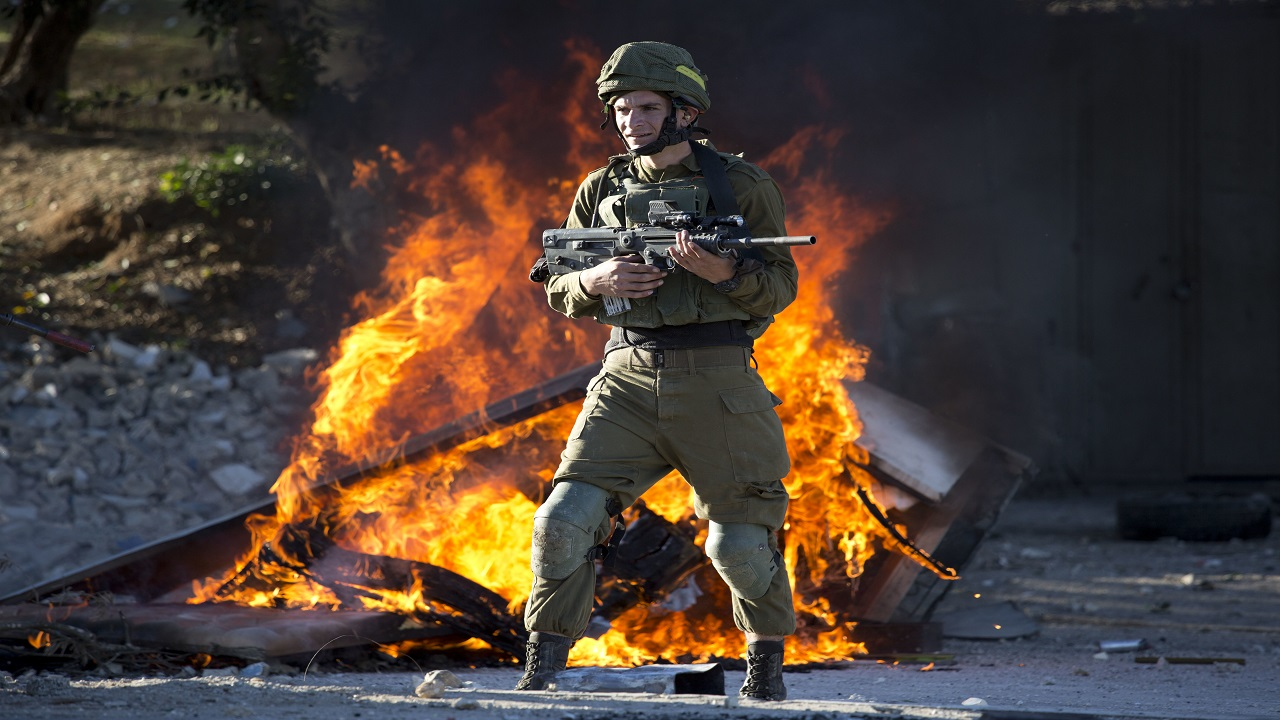 Israeli soldier stands during clashes with Palestinians following a protest against U.S. President Donald Trump's decision to recognize Jerusalem as the capital of Israel in the West Bank City of Nablus, Friday, Dec. 8, 2017.