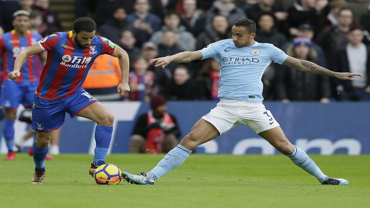Crystal Palace's Andros Townsend, left, competes for the ball with Manchester City's Ilkay Gundogan during the English Premier League football match at Selhurst Park in London, Sunday Dec. 31, 2017.