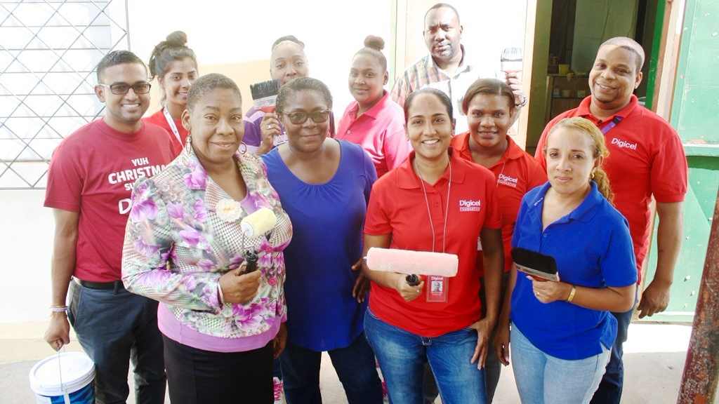 Digicel Foundation Project Coordinator, Diana Mathura-Hobson (front row 2nd from right) along with members of staff, parents, volunteers and Digicel staff is set with the tools of the trade to repaint the Servol Special Needs School