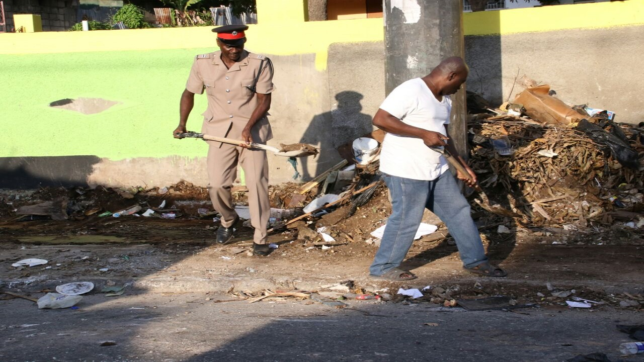 Inspector of Police and Sub-Officer in Charge of the Vineyard Town Police Station, Mark Harris assists a man clear debris dumped illegally in front of a house in Mountain View on Tuesday. (PHOTOS: Llewellyn Wynter)