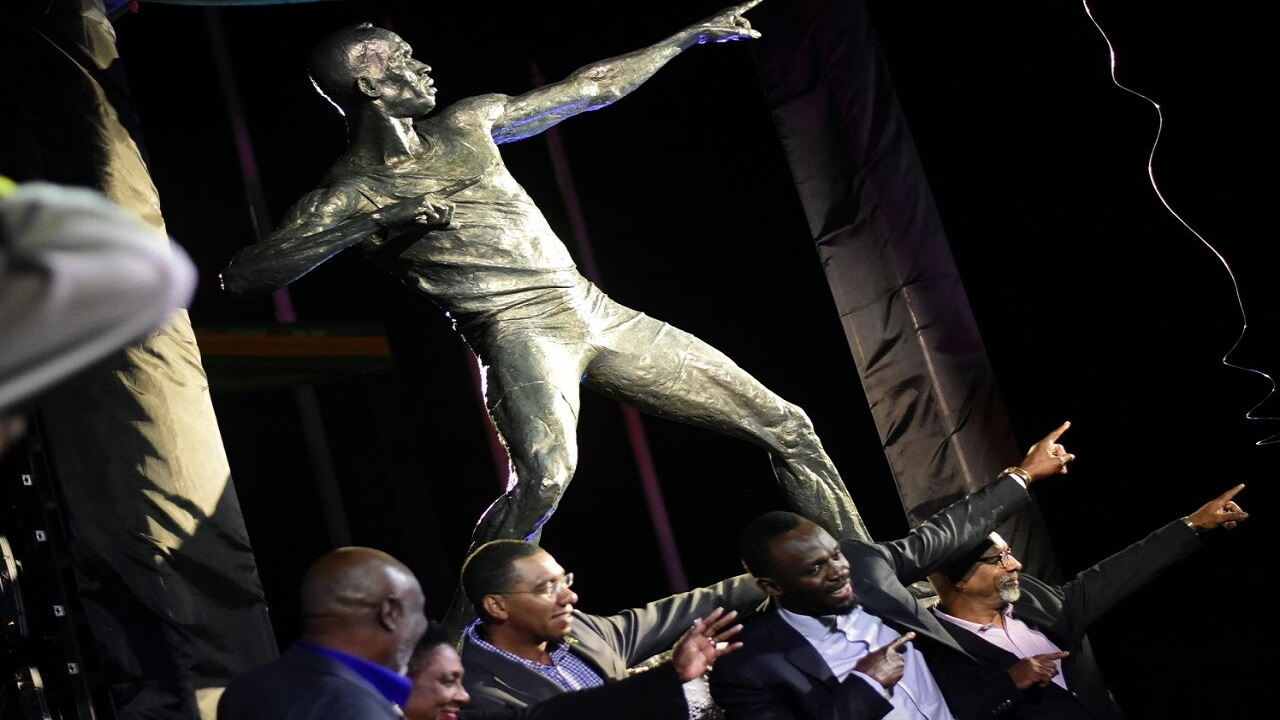 Jamaican sprint legend Usain Bolt (second right) does his trademark 'to the world' pose in front of a statue of his likeness at the National Stadium in Kingston on Sunday. He's joined by (from left) his coach Glen Mills, Sport Minister Olivia Grange, and Prime Minister Andrew Holness. (PHOTOS: Marlon Reid)