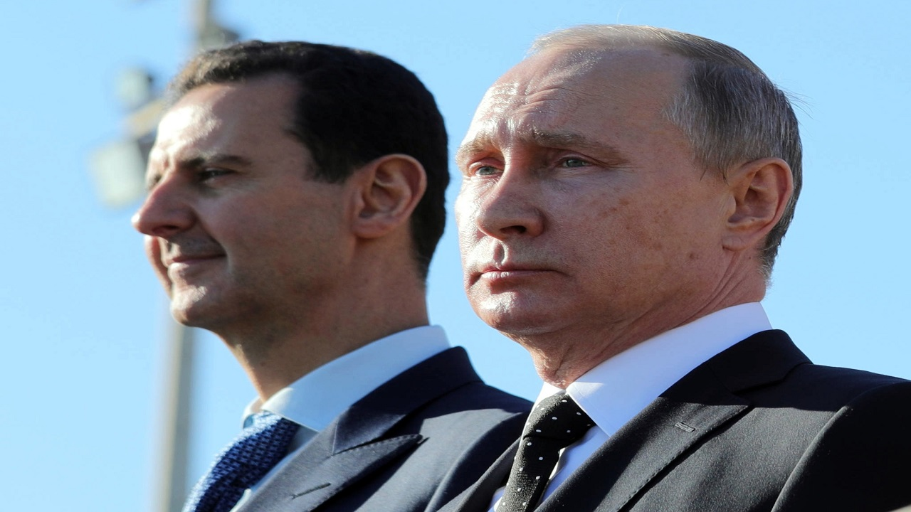 This Monday, Dec. 11, 2017 file photo, Russian President Vladimir Putin, right, and Syrian President Bashar Assad watch the troops marching at the Hemeimeem air base in Syria.