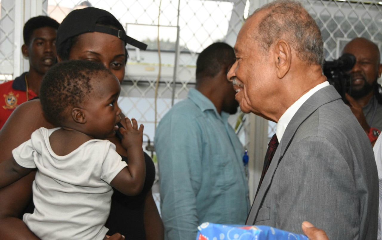 Mother and baby chatting with Sir Philip Greaves, Acting Governor General before he presented a Christmas gift to little one on the Paediatric Ward at the Queen Elizabeth Hospital.