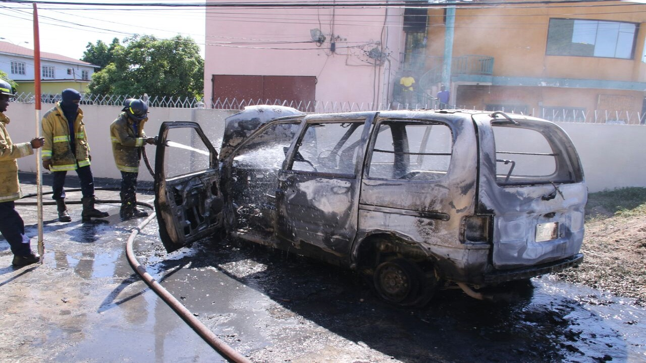 Firefighters spray water on the burnt out vehicle. (PHOTOS: Llewellyn Wynter)