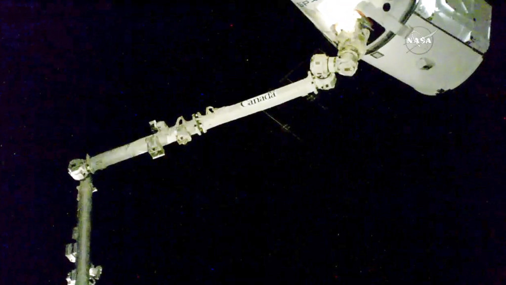 In this image taken from NASA Television, the robotic arm reaches out and captures the SpaceX Dragon cargo spacecraft for docking to the International Space Station.  (NASA via AP)