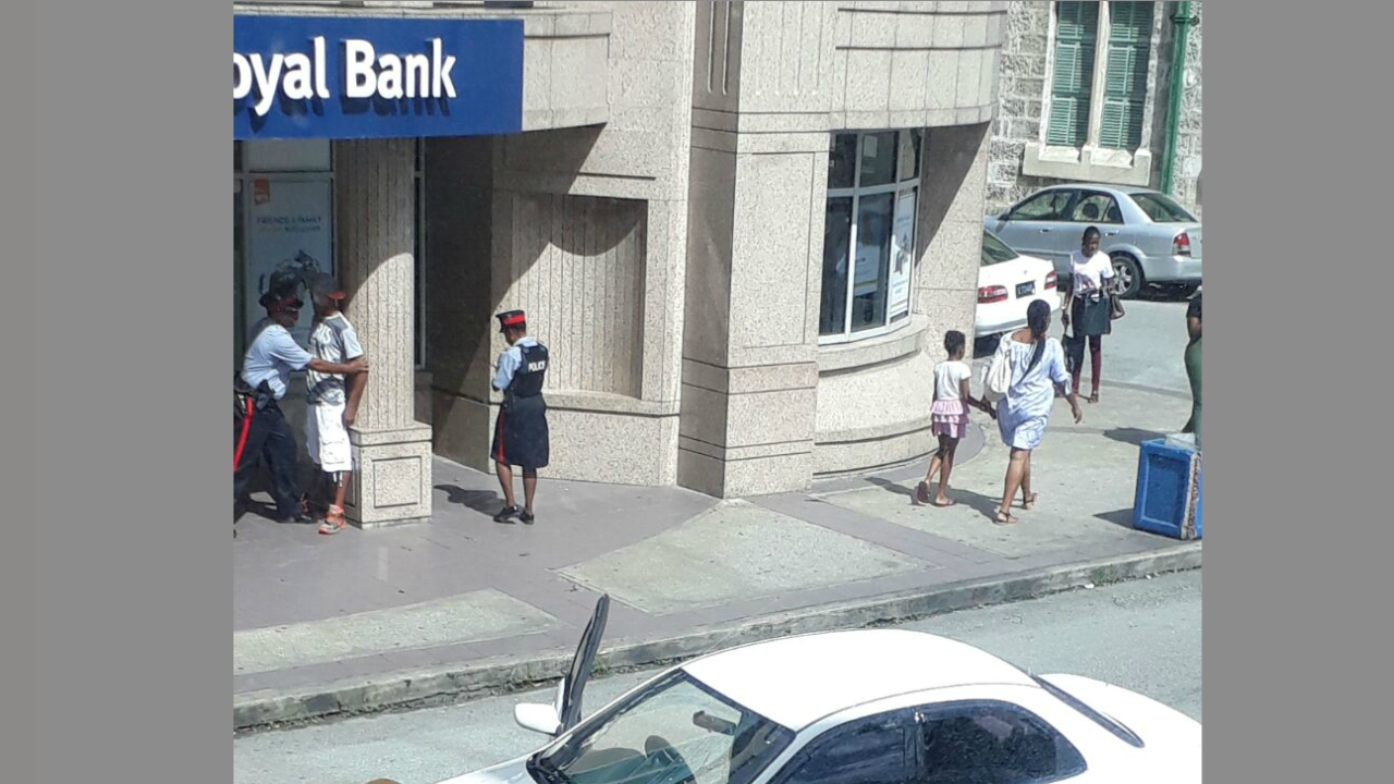 Police are pictured apprehending a man, while a car is parked facing the wrong direction on Broad Street, Bridgetown.