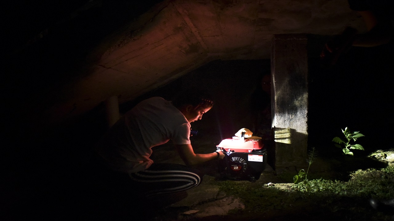 In this Dec. 21, 2017 filw photo, barrio Patron resident Karina Santiago Gonzalez works on a small power plant in Morovis, Puerto Rico. Puerto Rico authorities said on Friday Dec. 29, that nearly half of power customers in the U.S. territory still lack electricity more than three months after Hurricane Maria.
