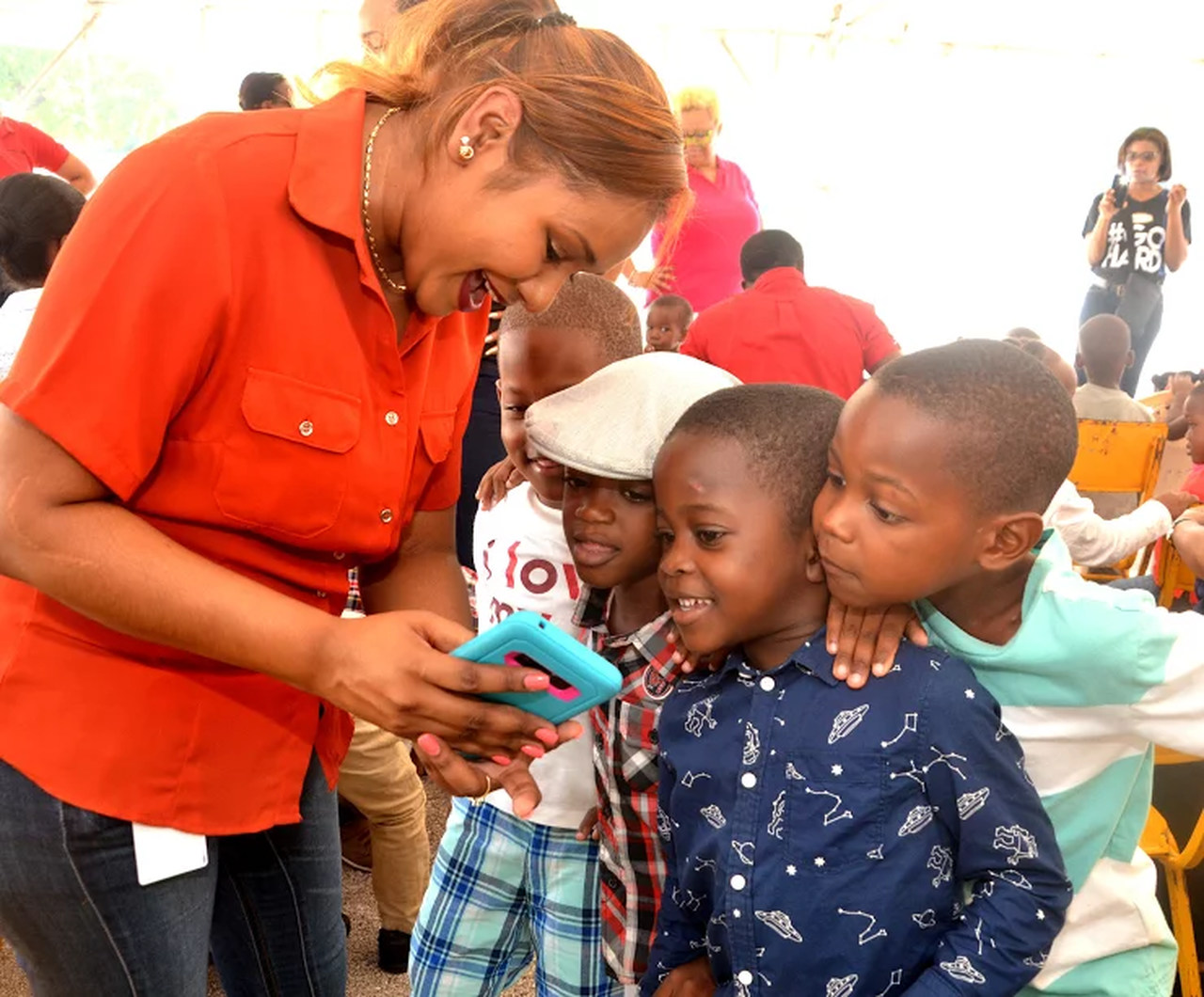 THIS IS SO COOL: Students of the Majesty Gardens Infant School are fascinated with the features of the phone being demonstrated by Kay-Ann Jackson, GraceKennedy's Human Resources Officer.  The students were at a Christmas treat put on by the Grace & Staff Community Development Foundation (GSCDF) at the Breezy Castle Sports Complex in downtown Kingston.