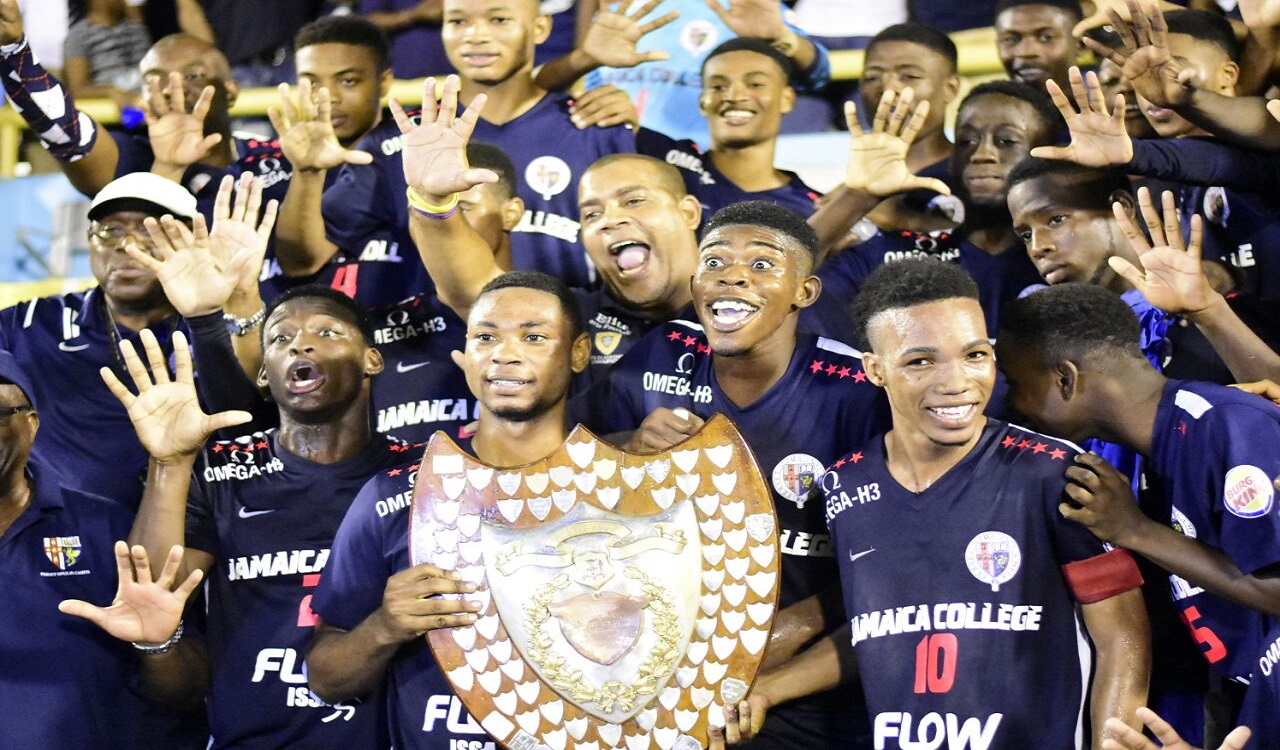Jamaica College players show off the Olivier Shield after defeating Rusea's High at the National Stadium on Saturday,