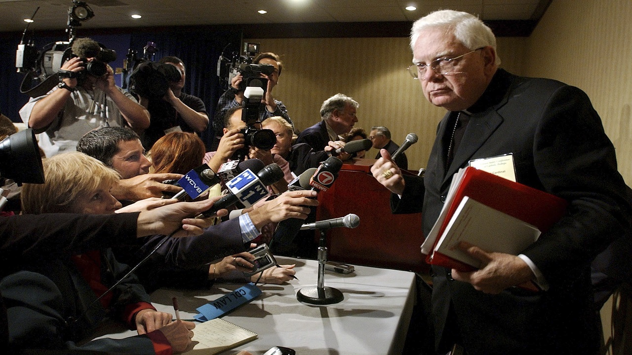 In this Tuesday, Nov. 12, 2002 file photo, Cardinal Bernard Law, right, departs a news conference during the second day of the U.S. Conference of Catholic Bishops annual meeting in Washington.