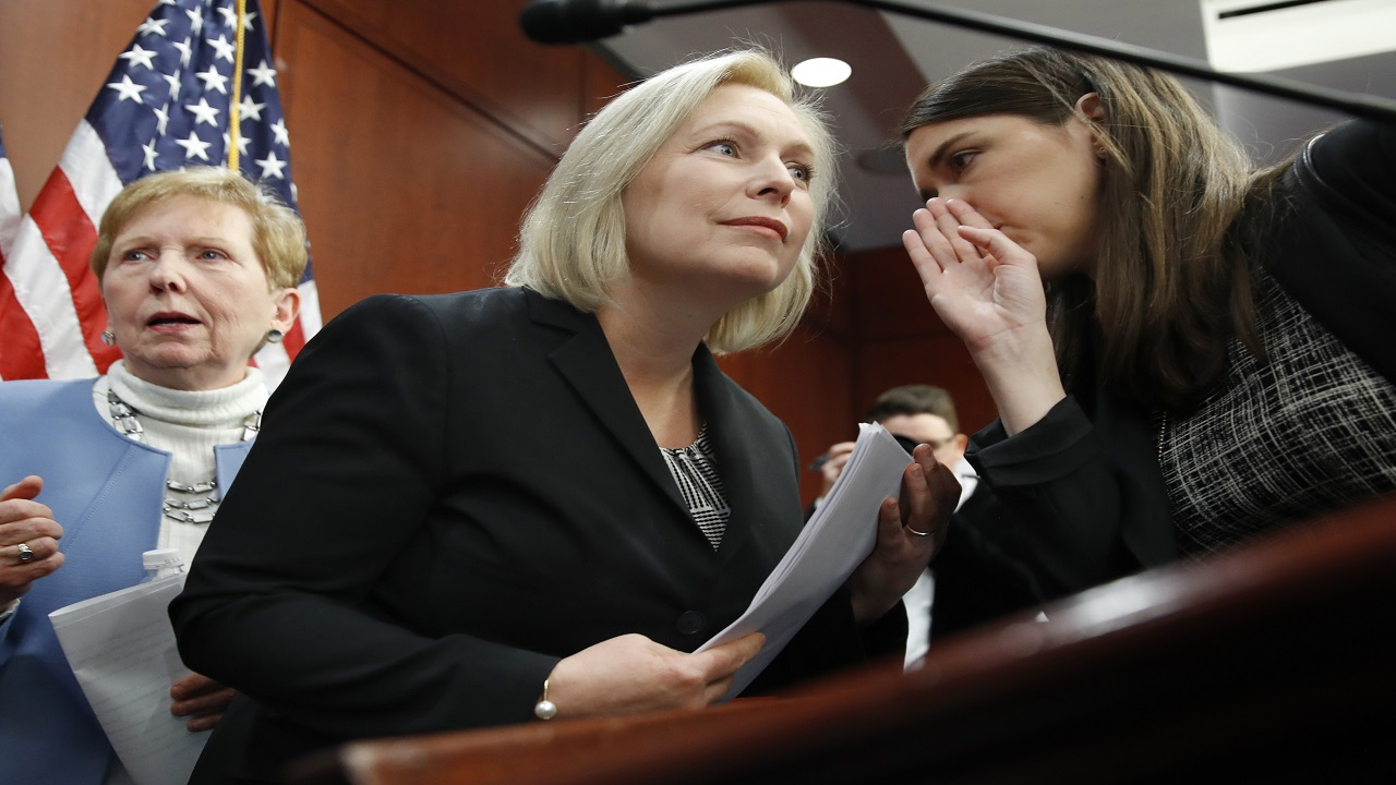 "Sen. Kirsten Gillibrand, D-N.Y., center, listens to a staffer before answering questions at a news conference, Tuesday, Dec. 12, 2017, on Capitol Hill in Washington. Gillibrand says President Donald Trump's latest tweet about her was a ""sexist smear"" aimed at silencing her voice."