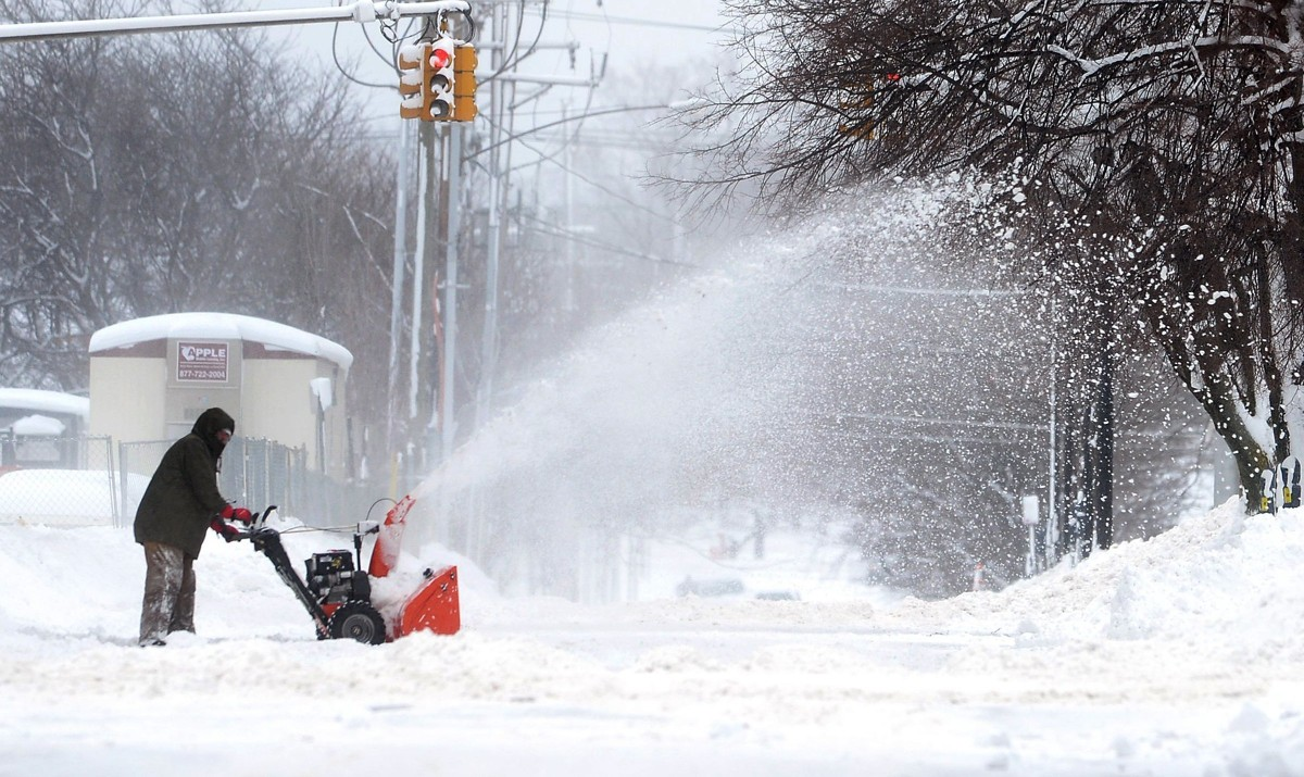 A man clears snow around his property. (Greg Wohlford/Erie Times-News via AP)