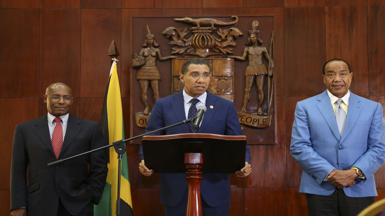 Prime Minister Andrew Holness (centre) addresses a press briefing on Tuesday where he hinted at crime plans as well as announced the appointment of Senator Aubyn Hill (left) as the executive director of the EGC. Looking on is EGC Chairman, Michael Lee-Chin (right).
