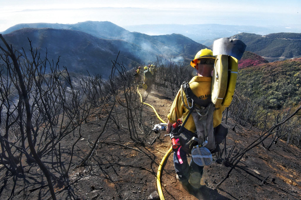 Santa Barbara County Firefighters haul dozens of pounds of hose and equipment down steep terrain below E. Camino Cielo to root out and extinguish smoldering hot spots in Santa Barbara, Calif., Tuesday, Dec. 19, 2017. Officials estimate that the Thomas Fire will grow to become the biggest in California history before full containment, expected by Jan. 7, 2018.