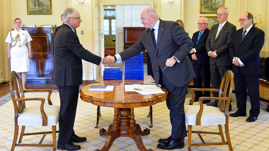 Commissioner Justice Peter McClellan, second left, shakes hands with Governor-General of Australia Peter Cosgrove, fourth right, at the signing ceremony and the release of the final report of the Royal Commission into Institutional Responses to Child Sexual Abuse at Government House, in Canberra, Dec. 15, 2017. The commission delivered its final 17-volume report and 189 recommendations following a wide-ranging investigation.
