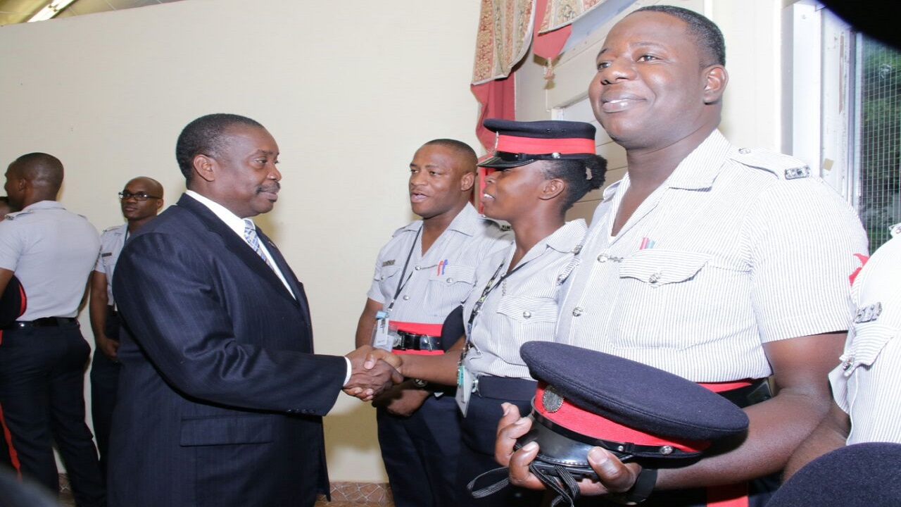 File photo of National Security Minister Robert Montague greeting police officers at an event.