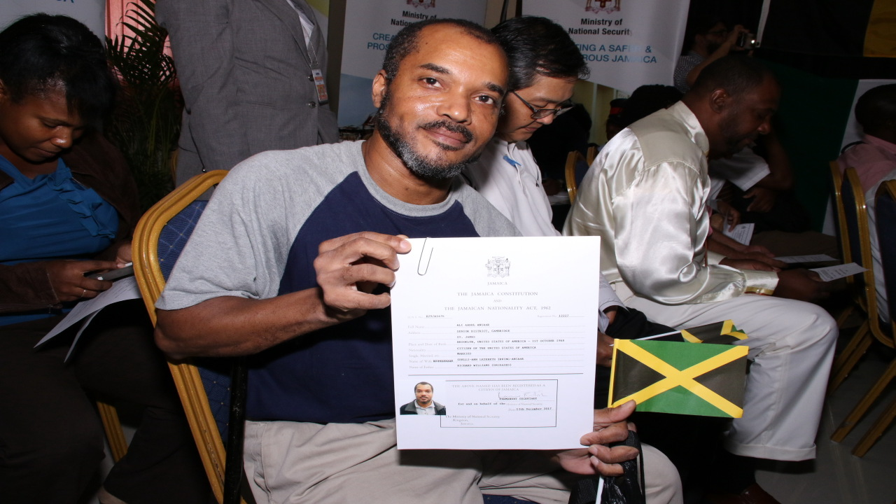 A newly minted Jamaican citizen shows off his documents at the Passport, Immigration and Citizenship Agency on Thursday. (PHOTOS: Llewellyn Wynter)